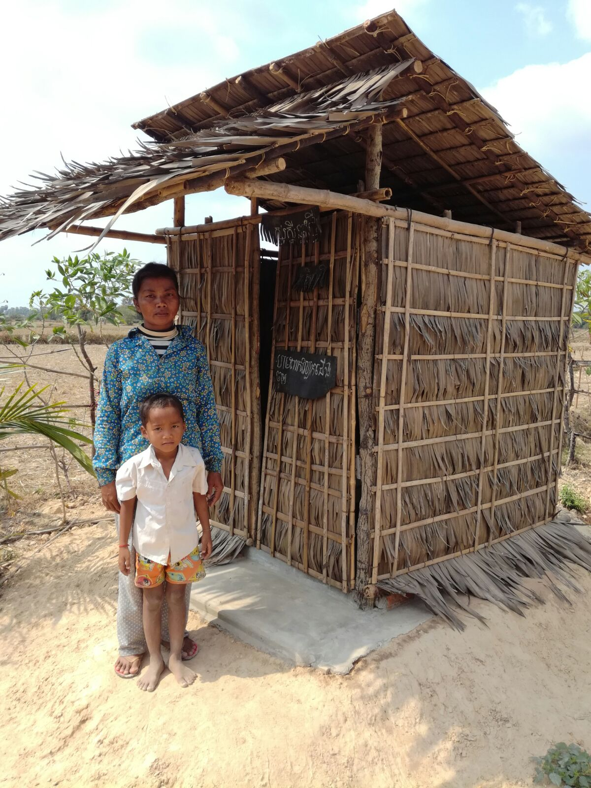 Hak Hun and Hak Nech pictured in front of their new toilet.